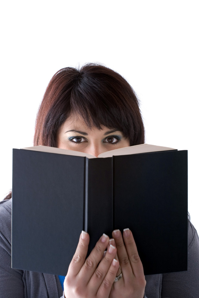 A young woman peeking over the top of a book she is holding up in front of her face.