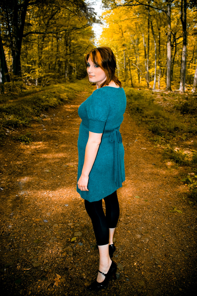 A young woman posing on a wooded path.