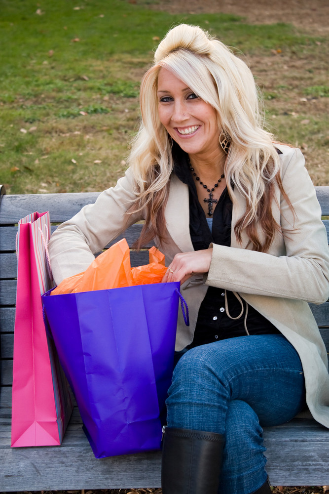 A young woman reaches into one of her many shopping bags.