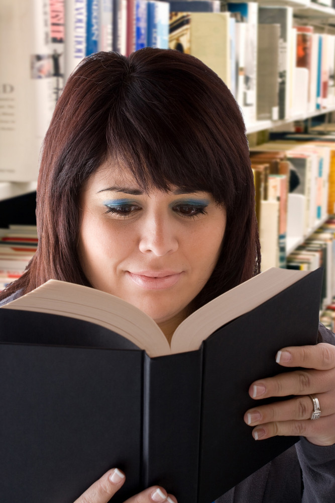 A young woman reading a book at the library.  Shallow depth of field.