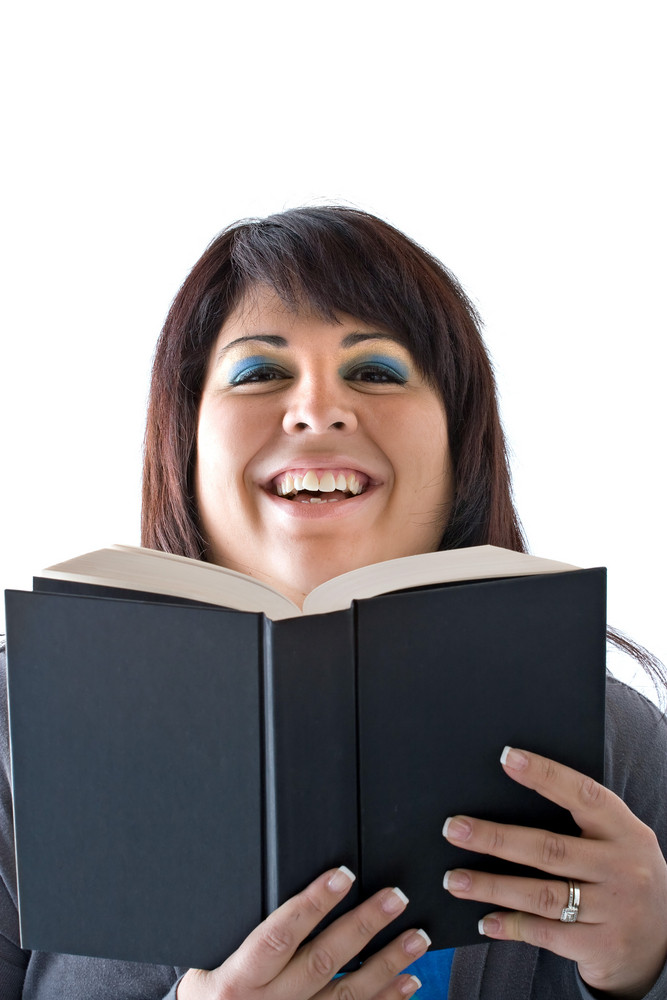 A young woman smiling as she reads a book.