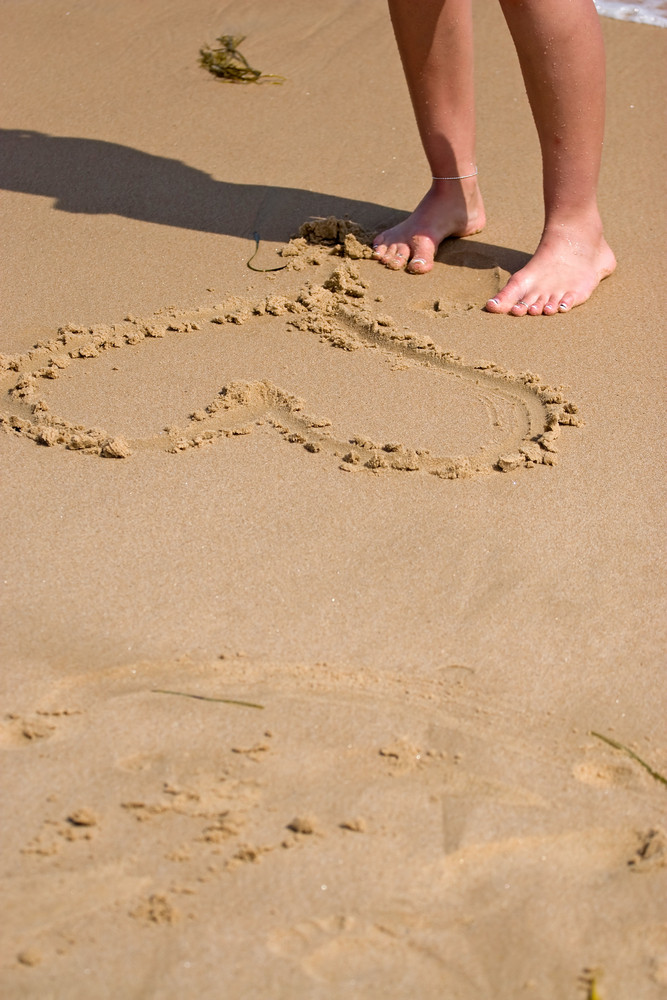 A young woman stands on the sandy shore by the heart she drew in the sand.