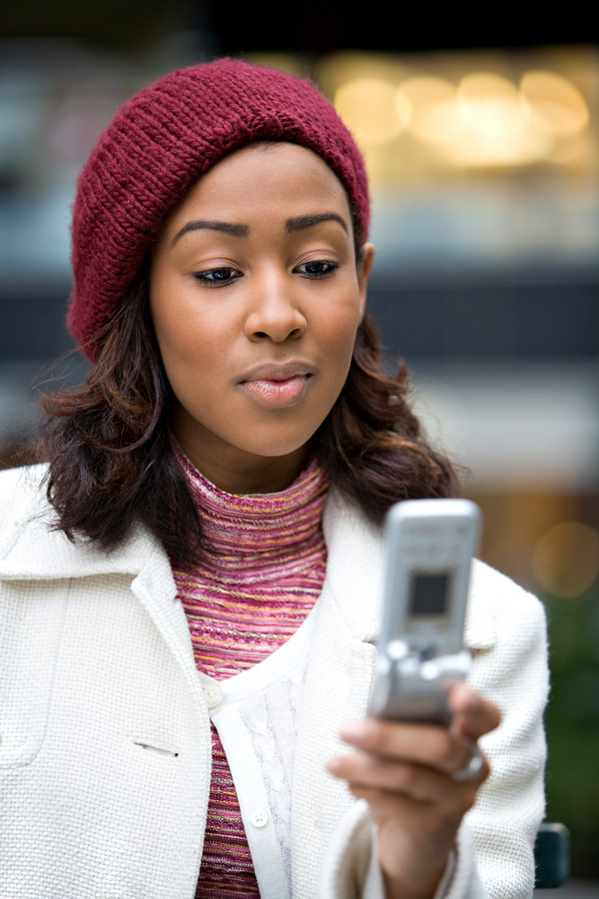 A young woman text messaging or checking email on her wireless phone.