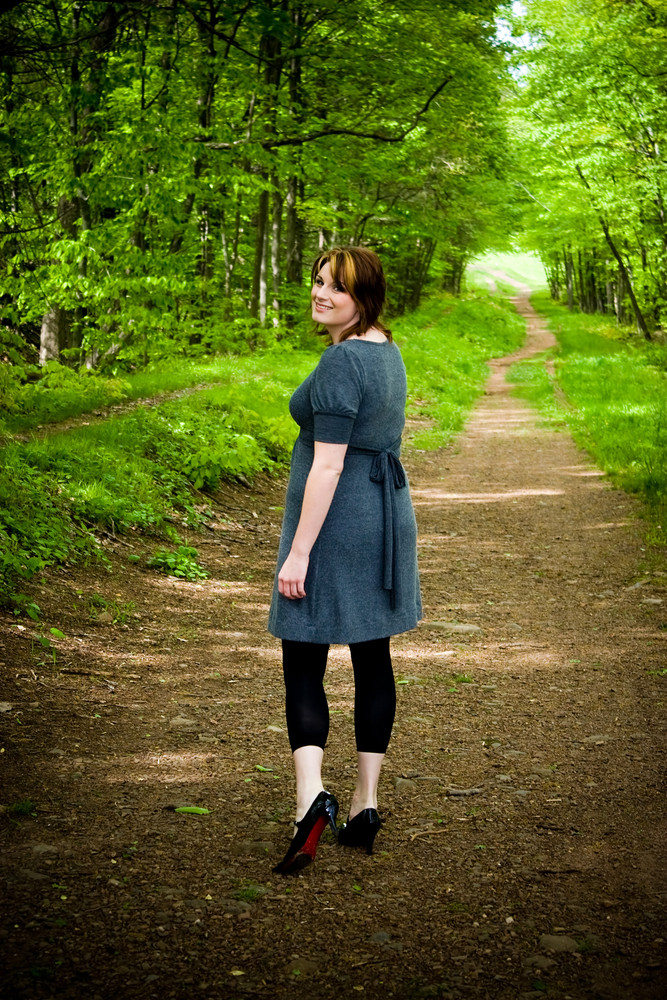 A young woman walking through a wooded path.