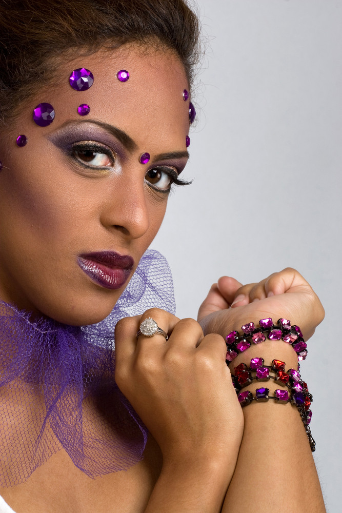 A young woman with gemstones on her face isolated over a silver backdrop.