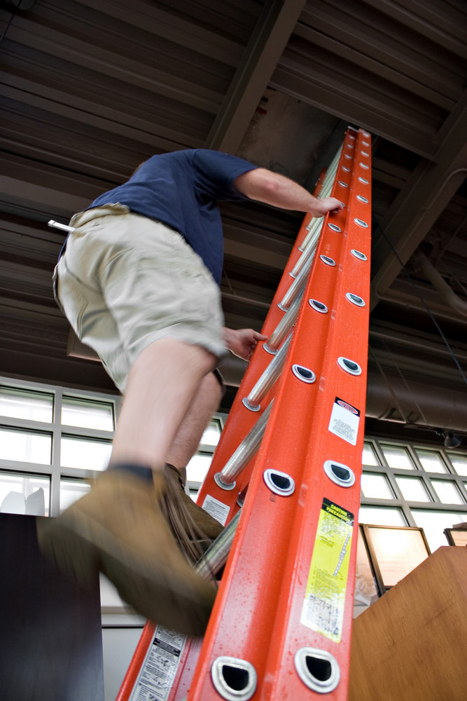 A young worker climbing up a ladder to enter through the hatch door in the ceiling.  Slight motion blur showing movement up the rungs.