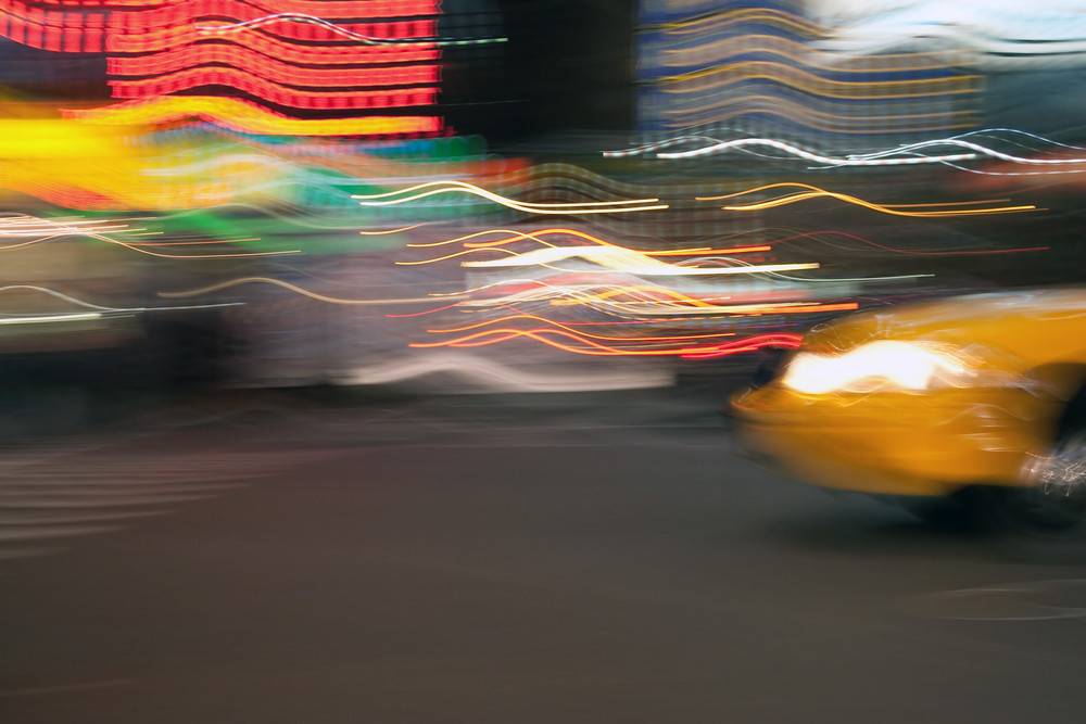 Abstract blur of a street scene in New York City with a yellow taxi cab speeding by. Slow shutter speed used for light trails and motion blur.