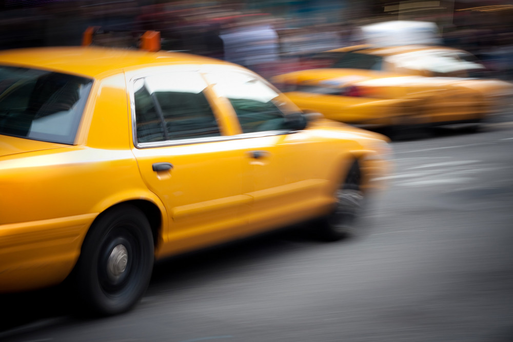 Abstract motion blur of a city street scene with a yellow taxi cabs speeding by.