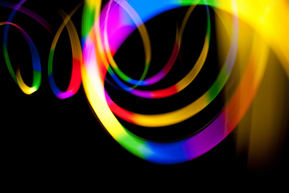 Abstract rainbow colored light streaks isolated over a dark black background.