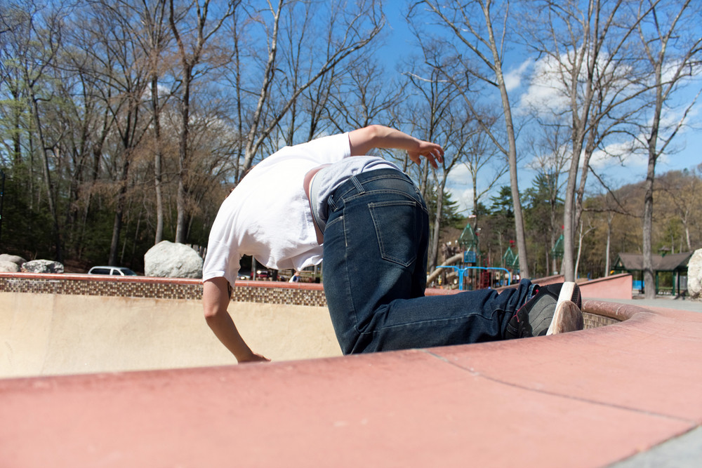 b55b149e Action shot of a young skateboarder skating sideways against the wall of  the bowl at a skate park.