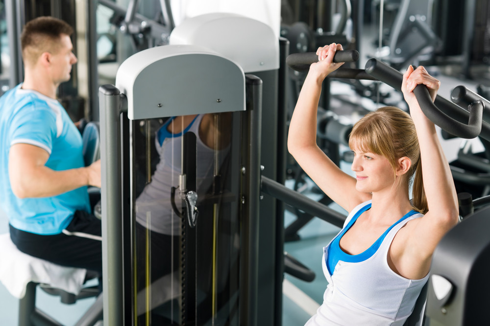 Active man and woman at fitness center exercise on machine