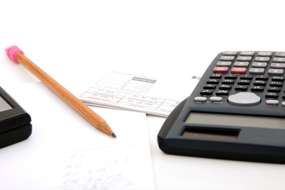 Adding up the monthly expenses for household accounting.  A calculator pencil and paperwork.  isolated over white.