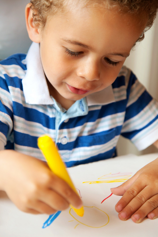 Adorable cute preschooler colors using a yellow crayon