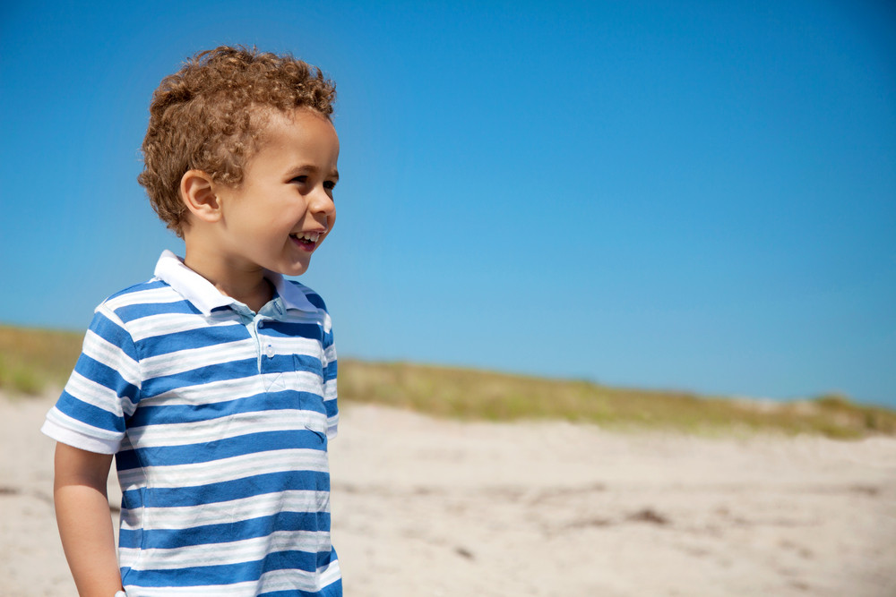 Adorable little boy enjoying the outdoors against the blue sky