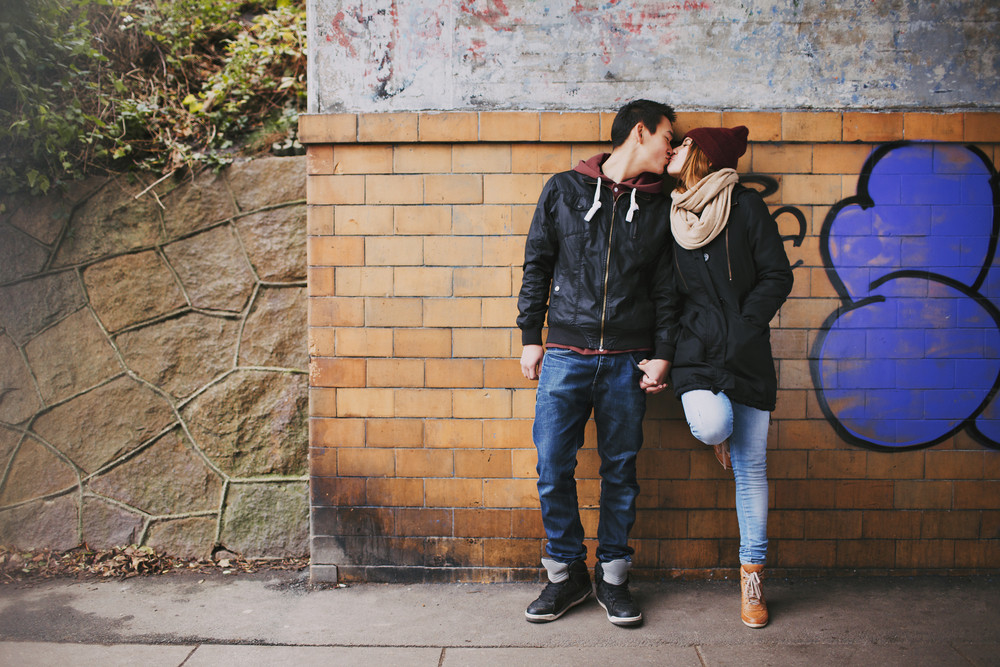 Affectionate teenage couple kissing outdoors against a wall on street. Mixed race couple in love.