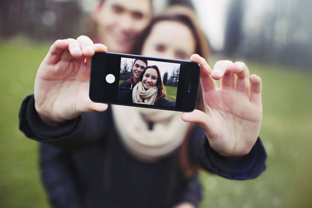 Affectionate young couple taking a self-portrait with a smartphone at the park. Mixed race teenage man and woman outdoors taking their picture with mobile phone.