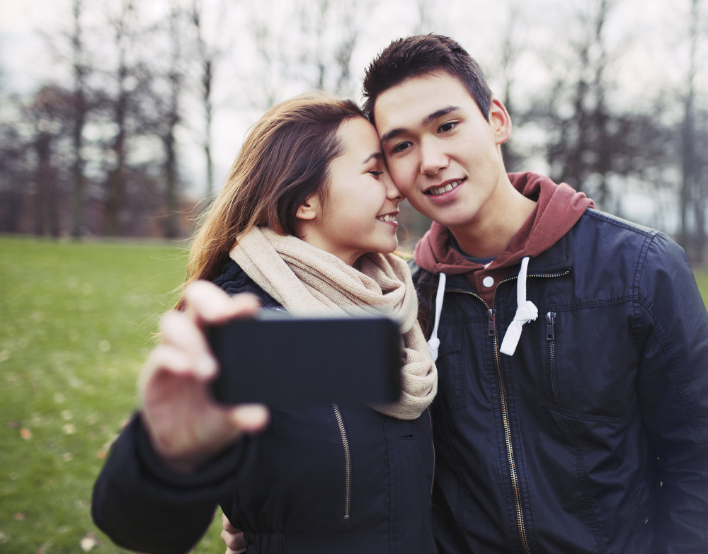Affectionate young couple taking pictures using a smart phone at the park. Teenage boy and girl in love photographing themselves outdoors.