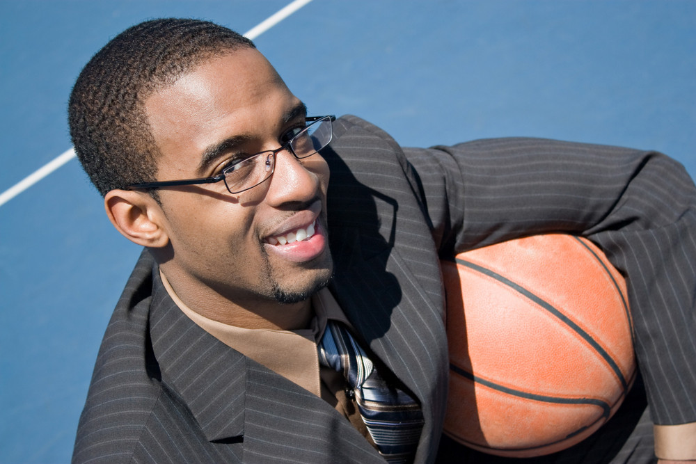 African American man in a business suit posing with a basketball.  He could be a coach player recruiter scout or trainer.