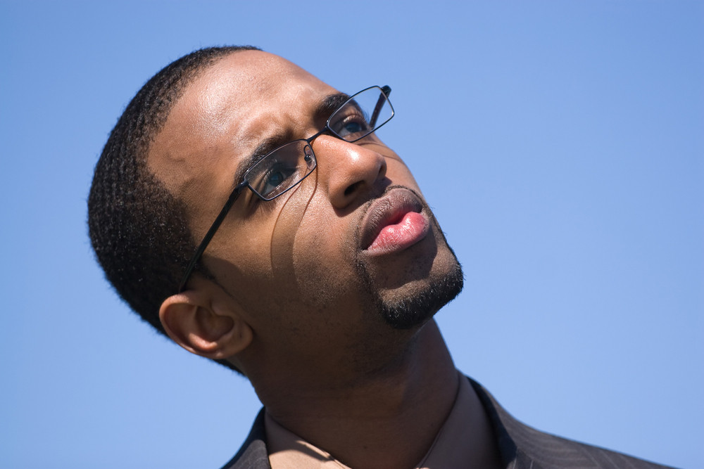 African American man wearing glasses and a business suit isolated over a blue background.
