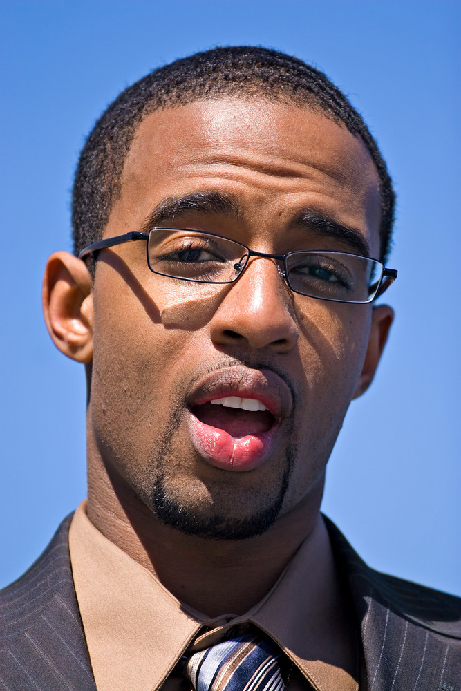 African American man wearing glasses and a business suit isolated over a blue sky background.