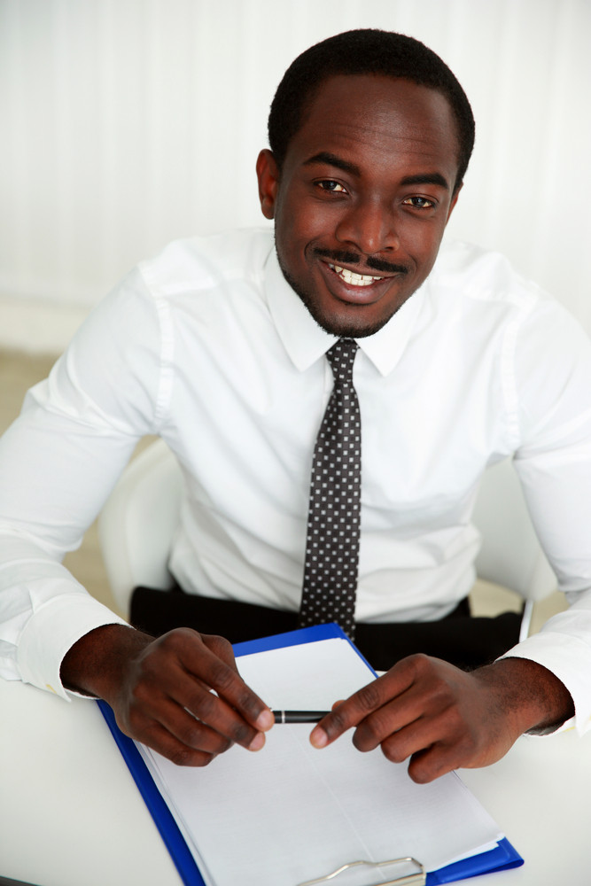 African man sitting at the table and signing document in office