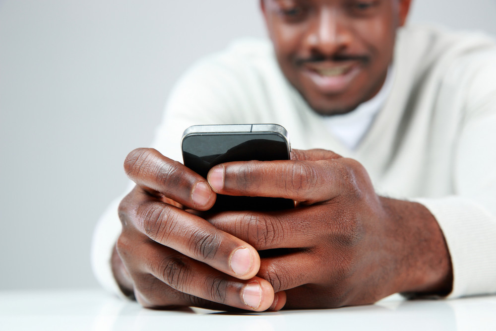 African man sitting at the table and using smartphone. Focus on smartphone