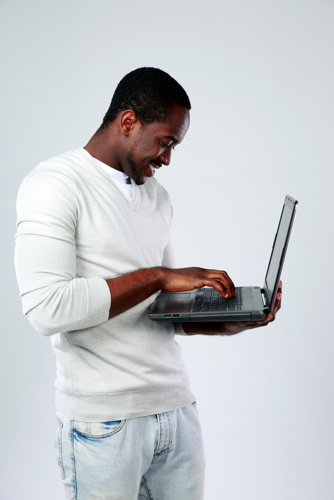 African man using laptop while standing up on gray background