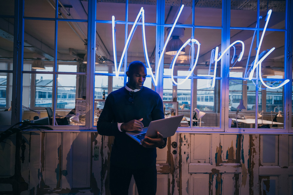 African young man standing in office using laptop computer. Business executive in office with big neon light work sign at the back on wall.