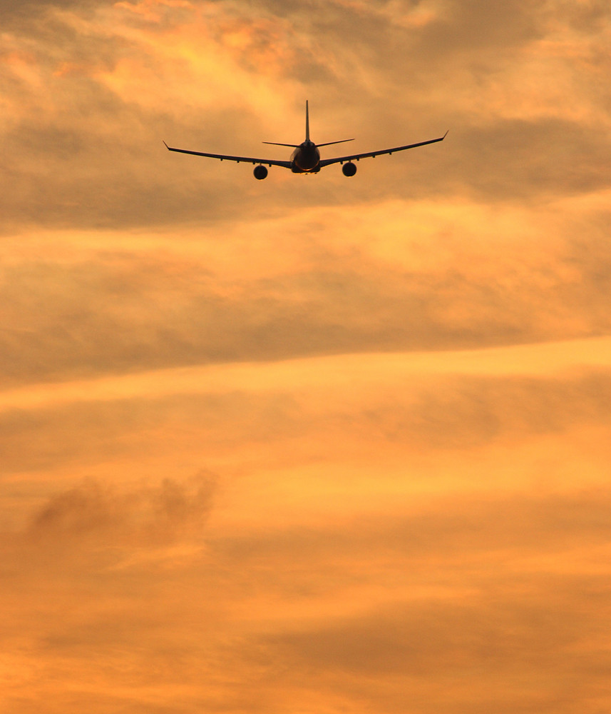 Airplane Flying To A Tropical Destination Into The Sunset