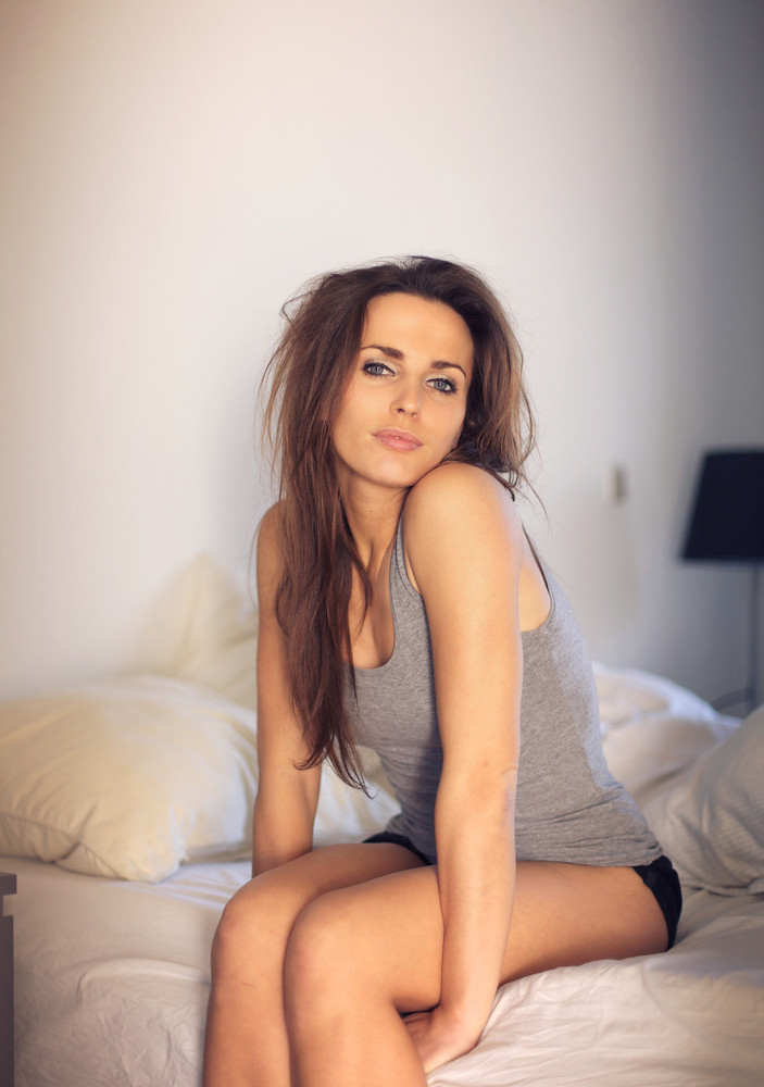 Alluring woman posing seductively while sitting on top of her bed