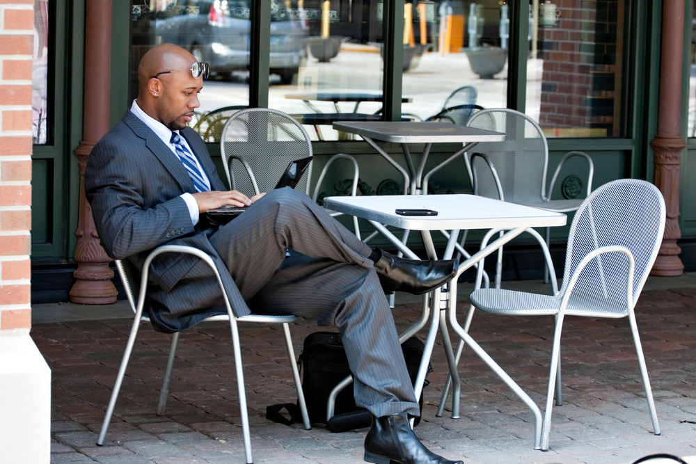 An African American business man in his early 30s using his laptop or netbook computer while seated at a cafe table outdoors.