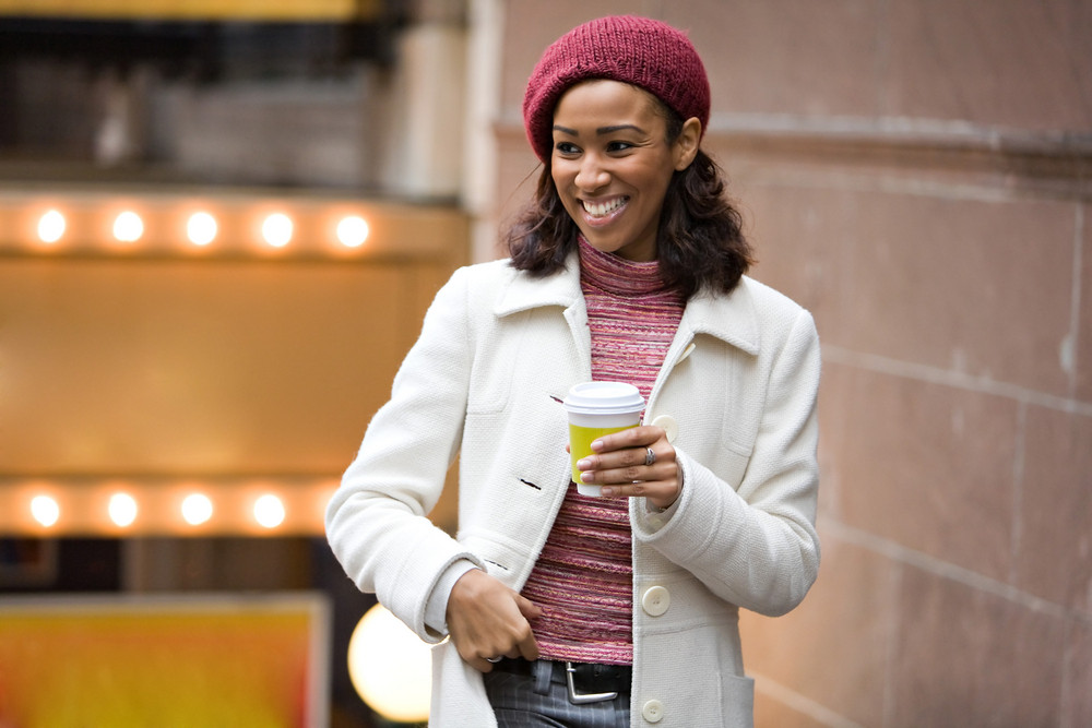 An African American business woman is walking through the city holding a cup of coffee tea or cappuccino.