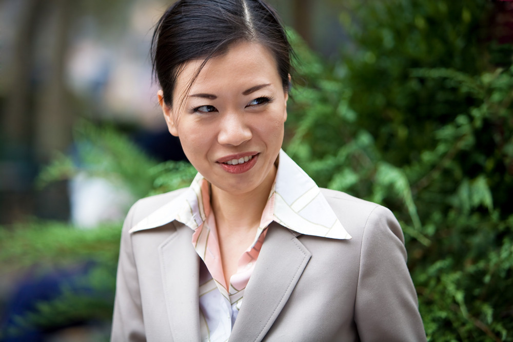 An attractive Asian woman dressed in business attire.