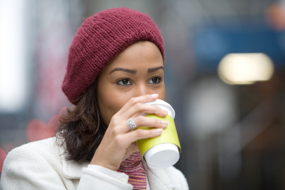 An attractive business woman enjoying a hot coffee in the city.