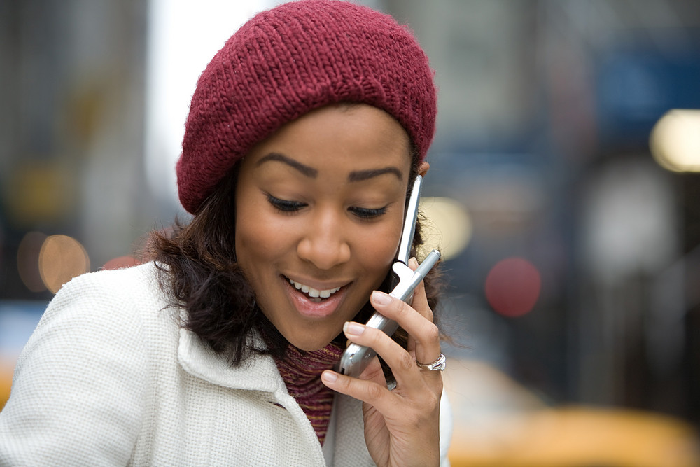 An attractive business woman talking on her cell phone in the city.