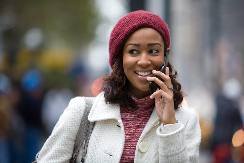 An attractive business woman talks on her cell phone as she walks through the city.