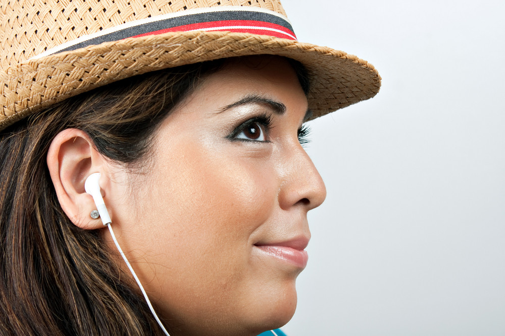 An attractive Hispanic woman listening to music playing through her stereo earbud headphones.