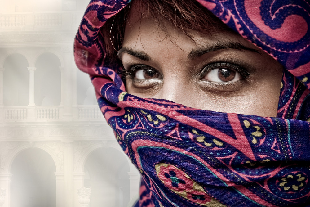 An attractive middle eastern woman wearing a colorful head covering.