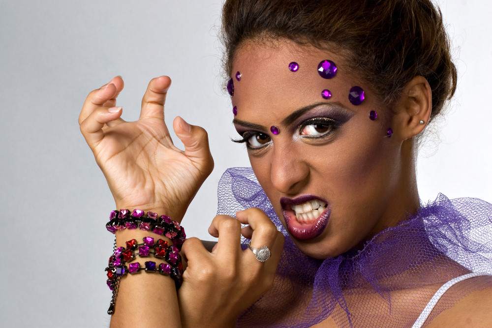 An attractive young model with glamorous makeup and gemstones in a fierce pose.