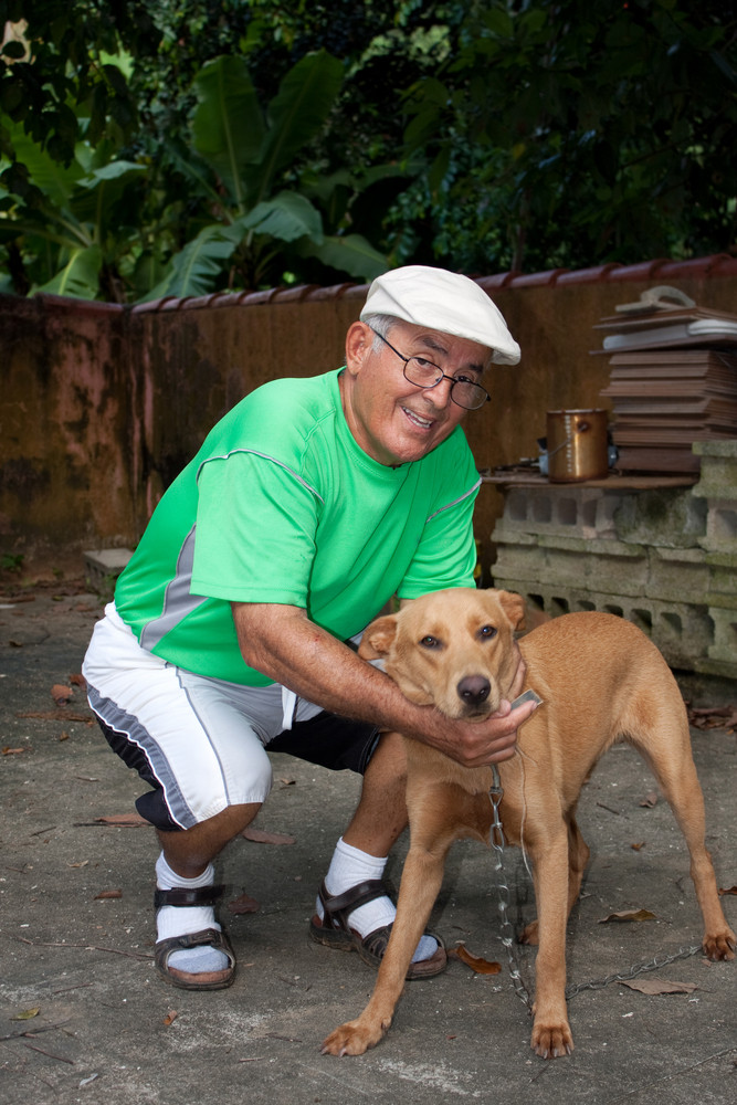 An elderly Hispanic senior citizen man petting his dog with a large smile on his face.