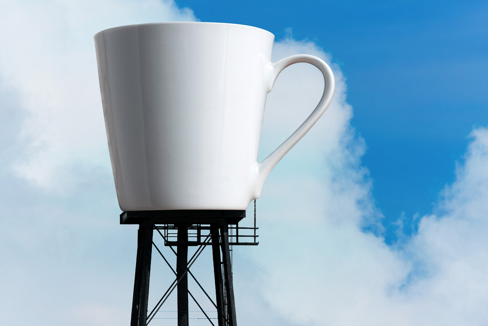 An enormous supply of coffee in the form of a coffee mug atop water tower stilts.  A funny concept for caffeine addiction or coffee lovers.