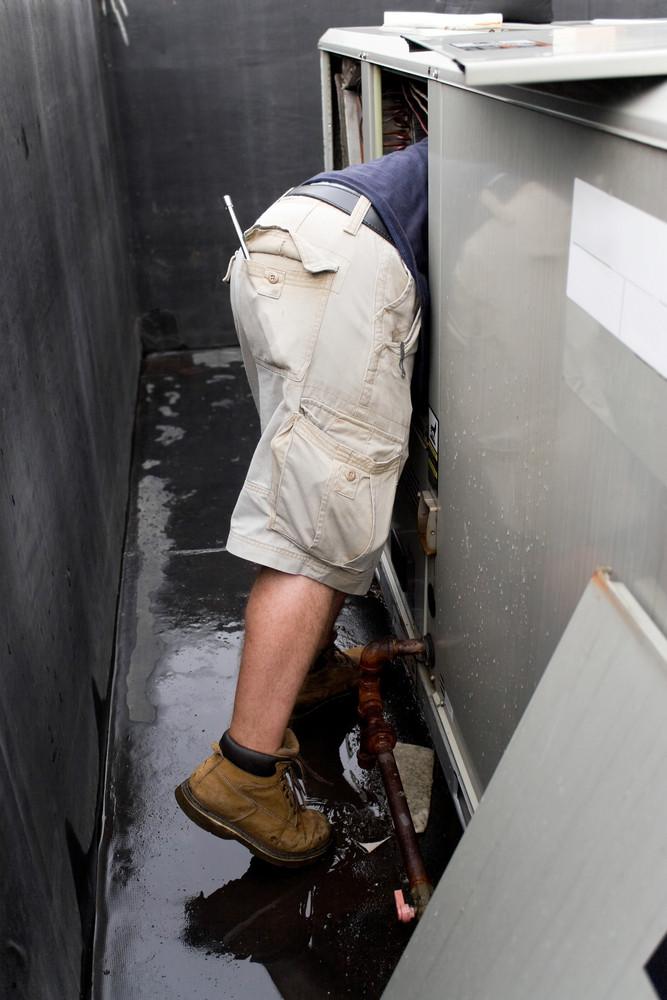 An HVAC technician repairing a commercial unit.
