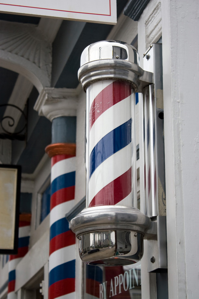 An old antique barber shop pole with red and blue stripes.
