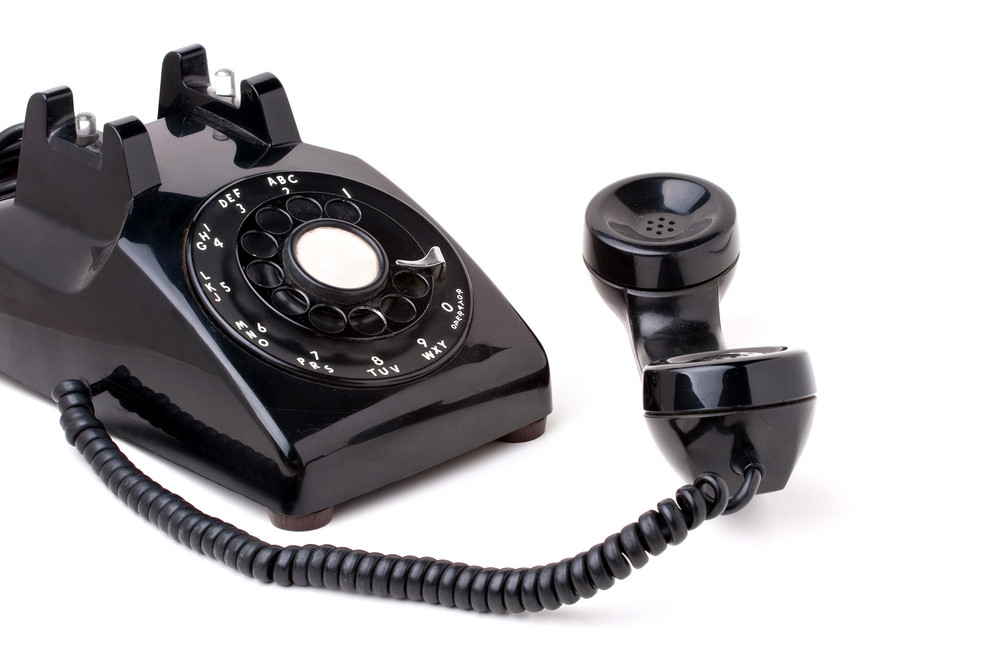 An old black antique rotary style telephone off the hook isolated over a white background.