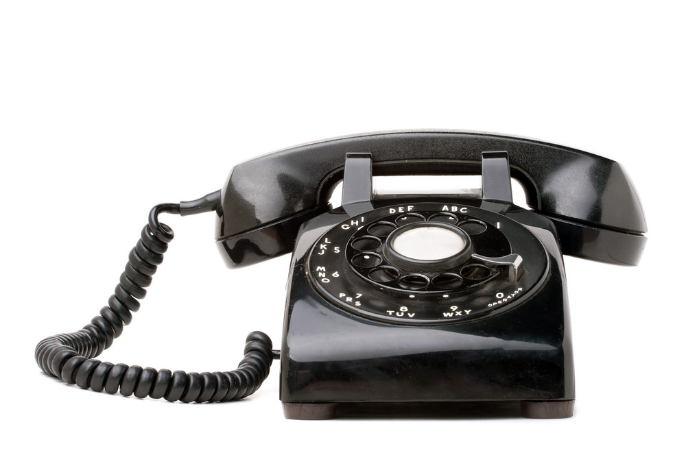 An old black vintage rotary style telephone isolated over a white background.