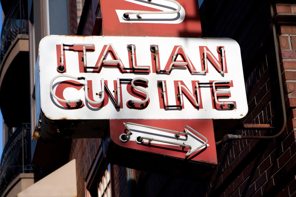 An old neon sign that reads ITALIAN CUISINE in glass tubing.