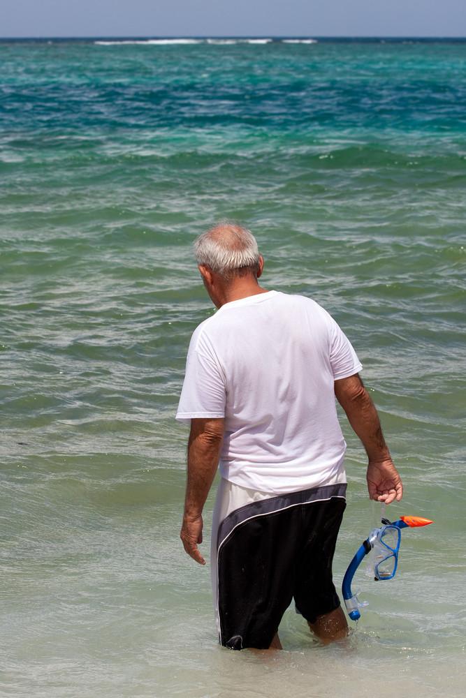 An older elderly man snorkels in tropical waters in the Caribbean off of the Puerto Rican island of Culebra.