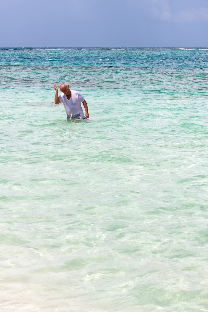 An older Senior citizen swimmer shakes the water out of his ear after snorkeling in tropical Caribbean waters off of the Puerto Rican island of Culebra.