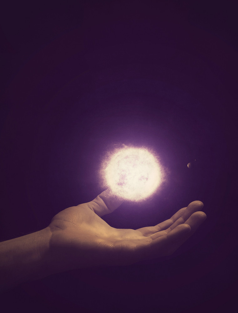 An open hand holding the solar system.