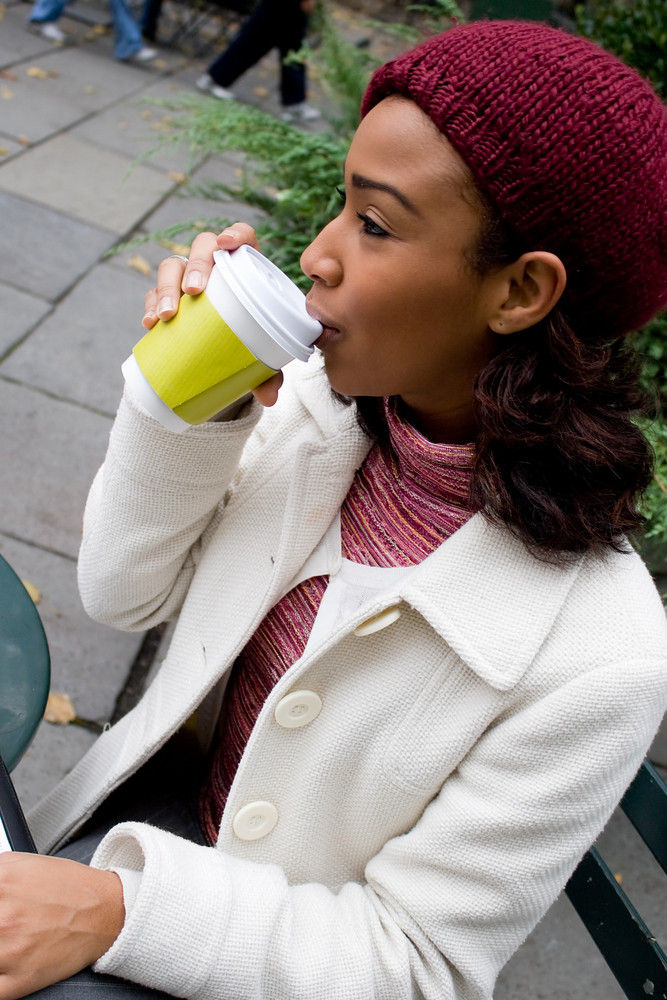 An young business woman takes a sip of her hot coffee or other beverage.